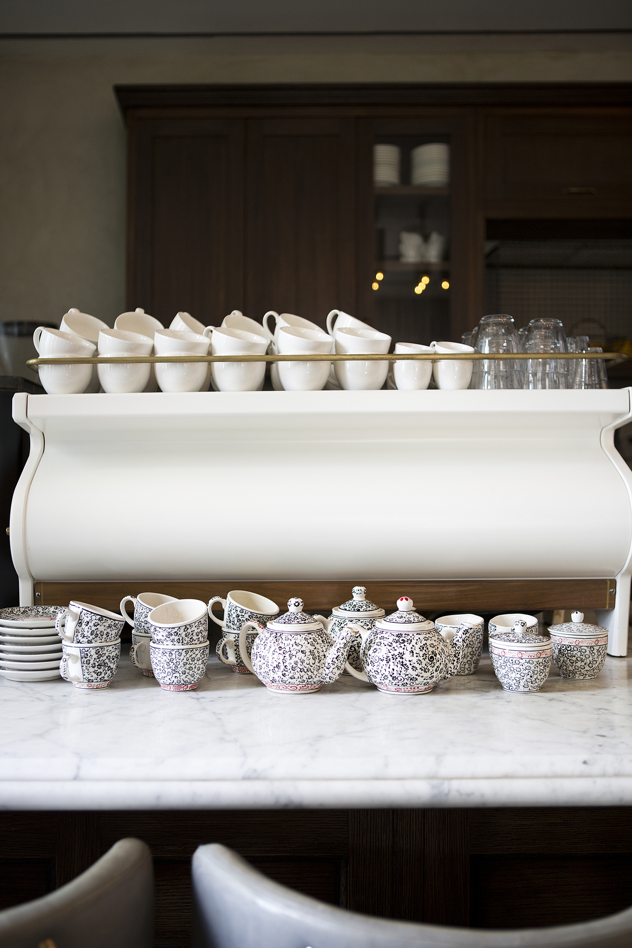 A coffee machine with stacks of patterned teacups