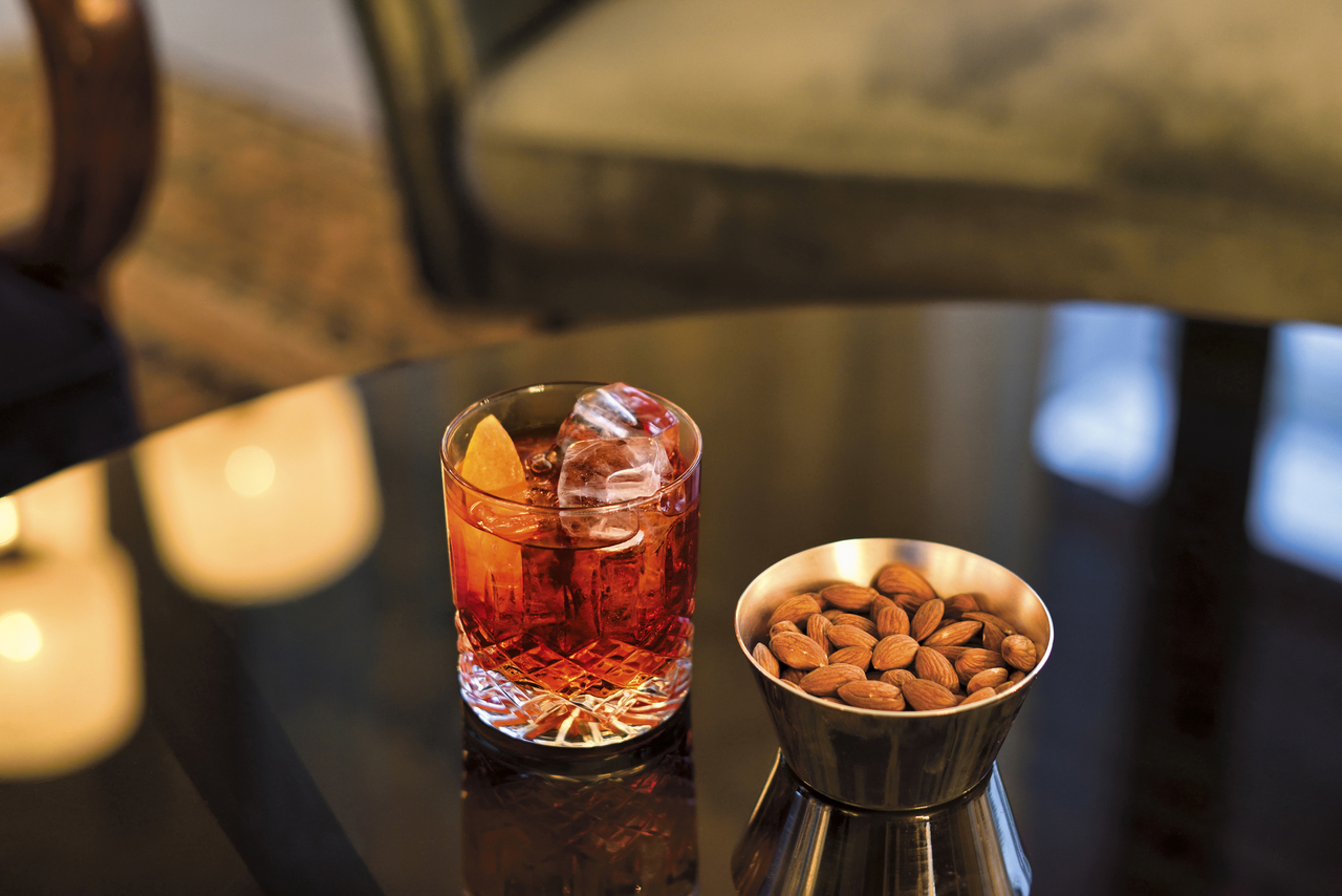 A Negroni and a snack bowl of almonds